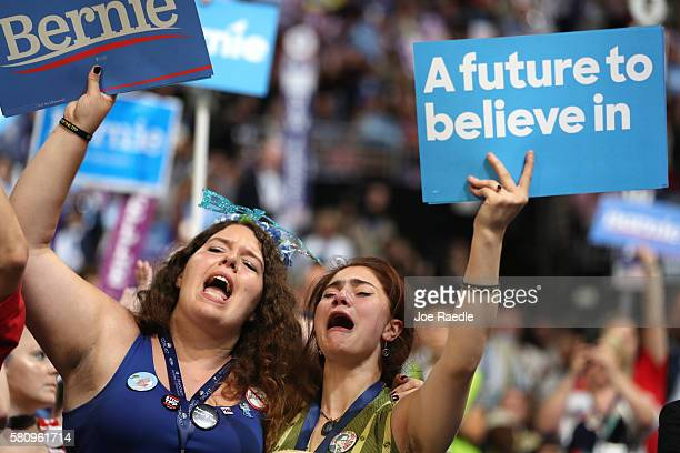 Supporters of Sen Bernie Sanders stand and cheer as he delivers remarks on the first day of the Democratic National Convention at the Wells Fargo...