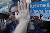 Supporters of Senator Bernie Sanders an independent from Vermont touch hands through the glass of the media tent while demonstrating during the...