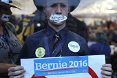 A supporters of Senator Bernie Sanders an independent from Vermont wears tape over his mouth reading 'No Voice' while demonstrating outside the media...