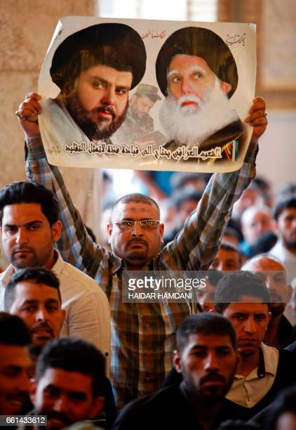 A supporters of Shiite cleric Moqtada alSadr holds a poster of him and his father Ayatollah Mohammed Sadeq alSadr during Friday prayers at the Great...