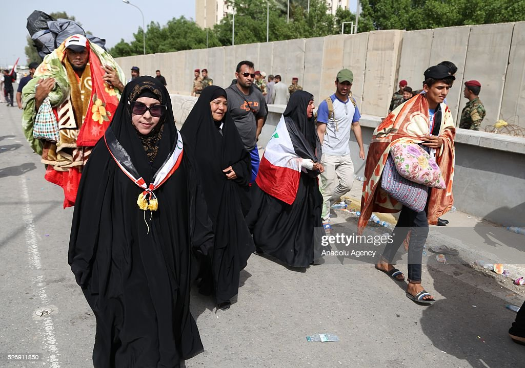 Supporters of Shiite cleric Muqtada al-Sadr carry their belongings to spend the night at Grand Festivities Square in Baghdad's Green Zone on May 1, 2016.