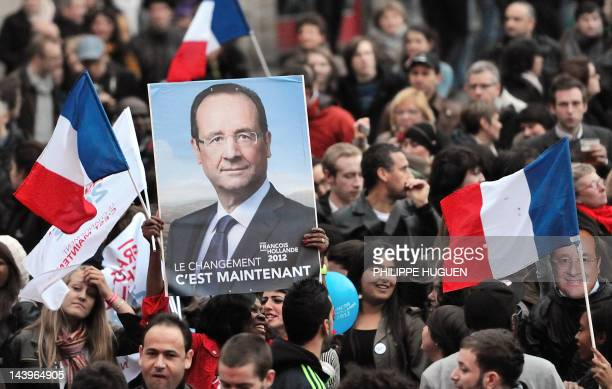 Supporters of Socialist Party newly elected president Francois Hollande celebrate holding a PS campaign poster and French national flags on May 6...
