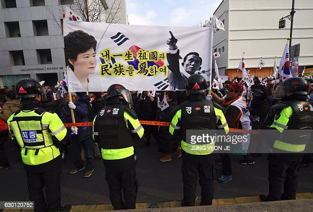 Supporters of South Korea's President Park GeunHye carry a large banner showing portraits of President Park and her father former dictator Park...