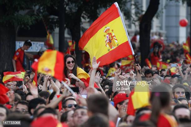 Supporters of Spain's national football team fly the national flag as they congratulate their team's players on their return to Madrid following...