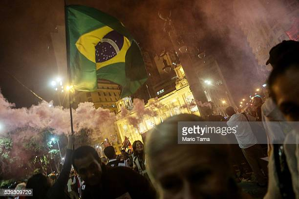 Supporters of suspended President Dilma Rousseff wave a Brazilian flag while protesting at a rally against interim President Michel Temer on June 10...