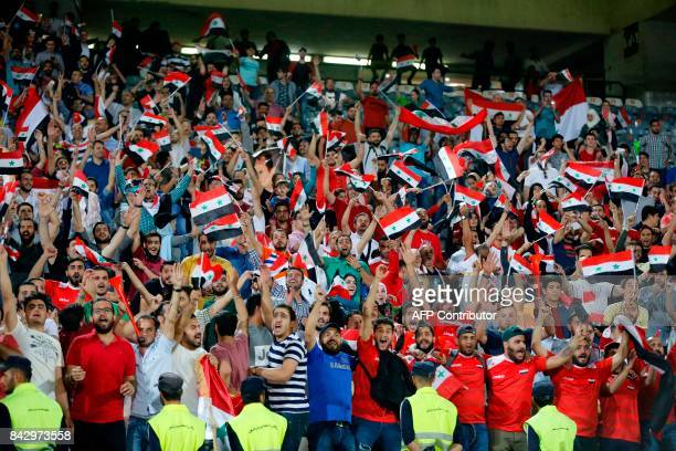 Supporters of Syria celebrate at the end of the FIFA World Cup 2018 qualification football match between Iran and Syria at the Azadi Stadium in...