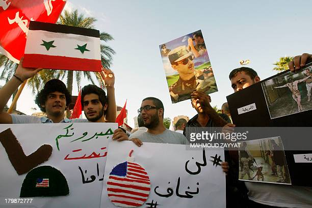 Supporters of Syrian regime raise up placards featuring Syrian President Bashar alAssad and pictures of Abu Ghraib prison in Iraq during a...