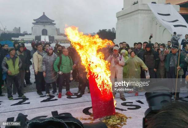 Supporters of Taiwanese independence burn a Republic of China flag in front of the Chiang Kaishek Memorial Hall in Taipei on Feb 28 during a...