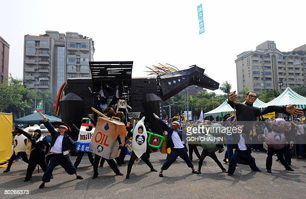 Supporters of Taiwan's presidential candidate Frank Hsieh of the ruling Democratic Progressive Party perform as sketch with a black wooden horse to...
