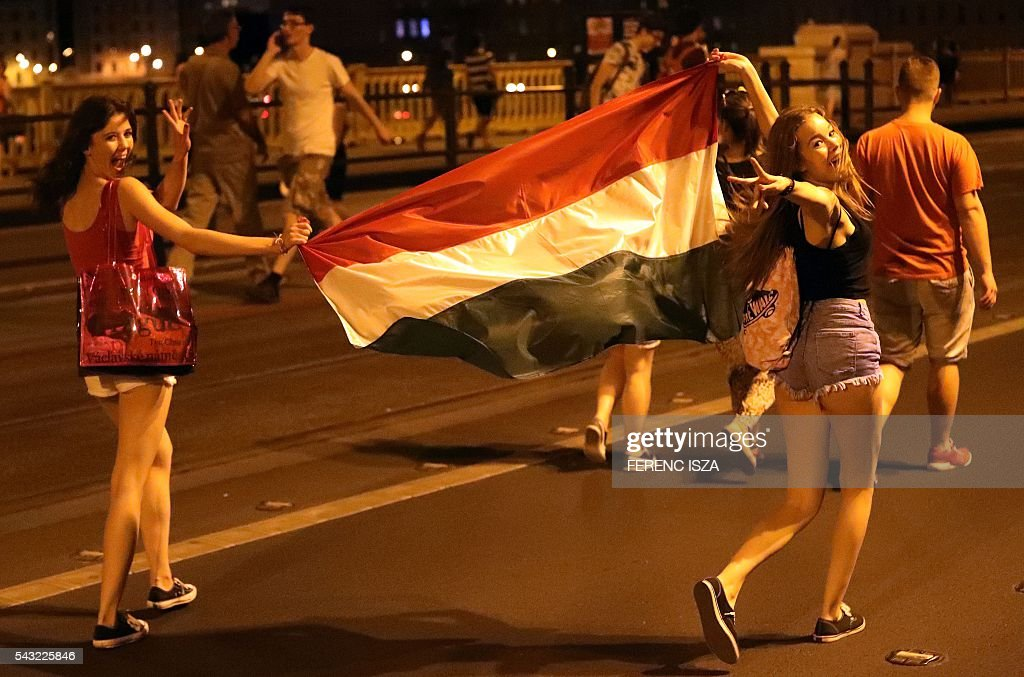 Supporters of team Hungary carry their national flag on June 26, 2016 in Budapest during the Euro 2016 football match against Belgium being played in Toulouse, France. Hungary lost 0-4. / AFP / FERENC