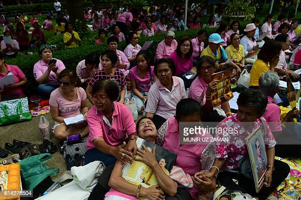 TOPSHOT Supporters of Thailand's King Bhumibol Adulyadej react as they pray at Siriraj Hospital where the king is being treated in Bangkok on October...