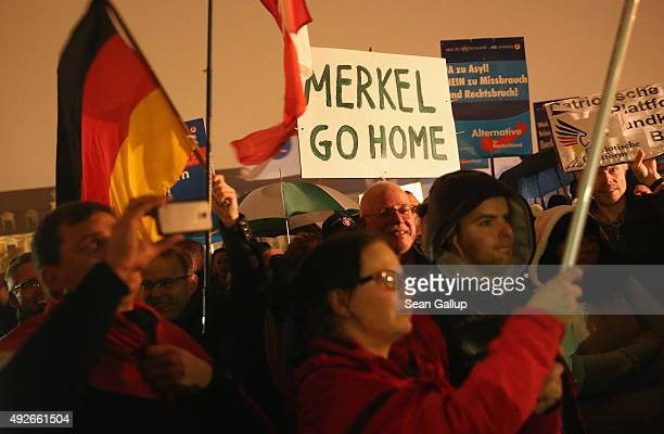 Supporters of the AfD political party protest against German Chancellor Angela Merkel's liberal policy towards taking in migrants and refugees on...