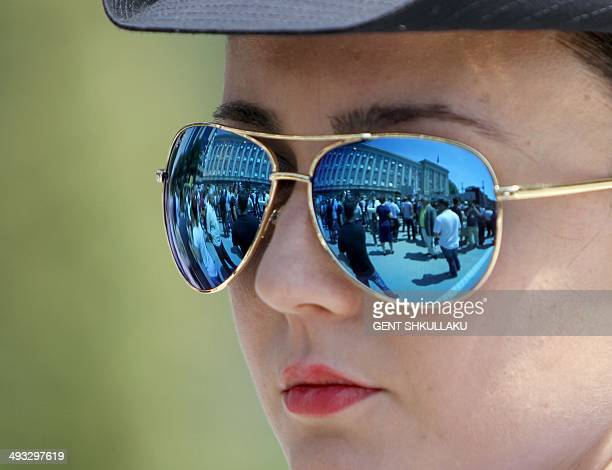 Supporters of the Albanian opposition are reflected on a police officer sunglasses as they protest in front of the government building in Tirana on...