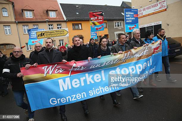 Supporters of the Alternative fuer Deutschland political party including AfD head in Thuringia Bjoern Hoecke march with a banner that reads 'Stop...