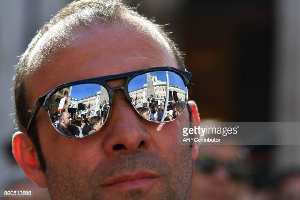 Supporters of the antiestablishment populist 5 Star Movement are reflected in sunglasses during a protest outside the lower house of parliament...