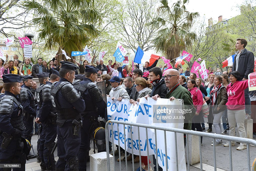 Supporters of the anti-gay marriage movement 'La Manif Pour Tous' (Demonstration for all) hold a banner facing riot policemen on April 26, 2013 in Marseille, southern France, to protest while French Justice Minister visiting the Marseille's courthouse (TGI).