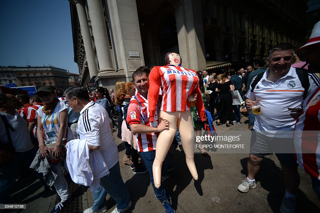 Supporters of the Atletico Madrid football club cheer their team at the Galleria Vittorio Emanuele on the day of the Champions League final between Real Madrid and Atletico Madrid in Milan on May 28, 2016. Record ten-time champions Real, who won the inaugural trophy in 1956, are gunning for their 11th title from European football's premier club event two years after a stunning comeback victory over Atletico in Lisbon secured 'La Decima'. / AFP / FILIPPO