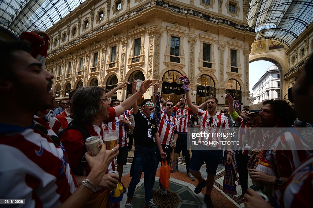 Supporters of the Atletico Madrid football club cheer their team inside the Galleria Vittorio Emanuele on the day of the Champions League final between Real Madrid and Atletico Madrid in Milan on May 28, 2016. Record ten-time champions Real, who won the inaugural trophy in 1956, are gunning for their 11th title from European football's premier club event two years after a stunning comeback victory over Atletico in Lisbon secured 'La Decima'. / AFP / FILIPPO