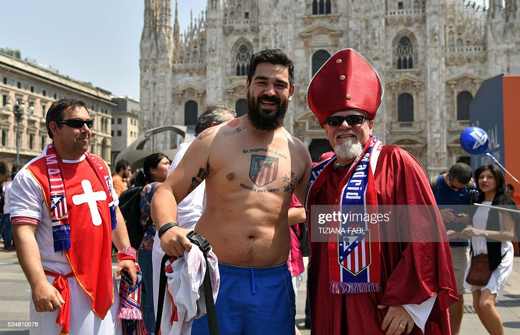 Supporters of the Atletico Madrid team pose during a gather at the Piazza Duomo - Duomo Square in Milan on May 28, 2016 on the day of the Champions League final between Real Madrid and Atletico Madrid. Record ten-time champions Real, who won the inaugural trophy in 1956, are gunning for their 11th title from European football's premier club event two years after a stunning comeback victory over Atletico in Lisbon secured 'La Decima'. / AFP / TIZIANA