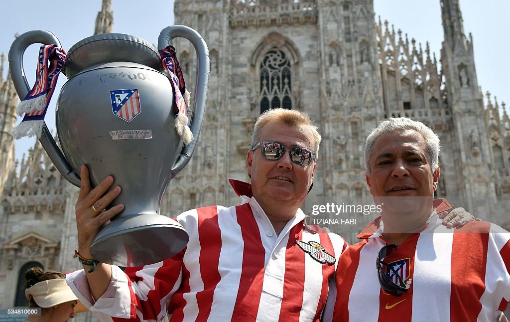 Supporters of the Atletico Madrid team wear the team jersey and hold an inflatable trophy at the Piazza Duomo - Duomo Square in Milan on May 28, 2016 on the day of the Champions League final between Real Madrid and Atletico Madrid. Record ten-time champions Real, who won the inaugural trophy in 1956, are gunning for their 11th title from European football's premier club event two years after a stunning comeback victory over Atletico in Lisbon secured 'La Decima'. / AFP / TIZIANA