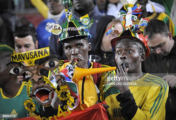 Supporters of the Bafana Bafana the South African football team play the vuvuzela large coloured plastic trumpet in the stands before the Fifa...