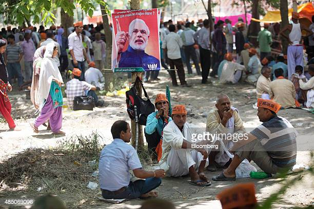 Supporters of the Bharatiya Janata Party sit under a poster featuring Indian Prime Minister Narendra Modi prior to a rally in Muzaffarpur Bihar India...