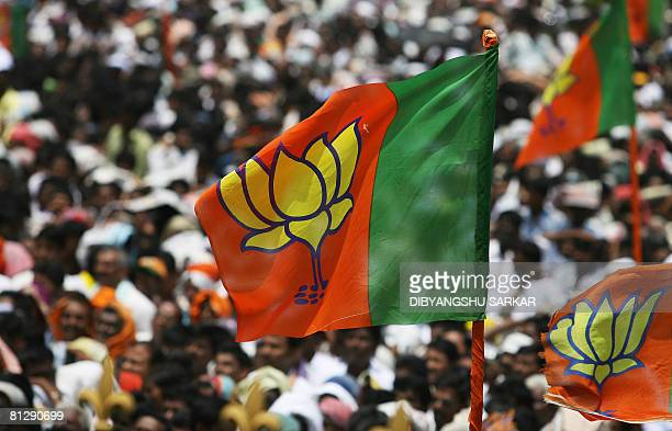 Supporters of the Bharatiya Janata Party wave party flag as they attend the swearingin ceremony in Bangalore on May 30 2008 BJP leader B S...
