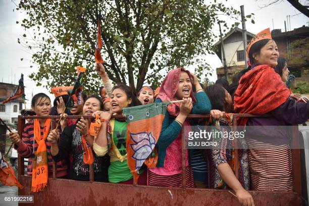 Supporters of the Bharatiya Janata Party wave their flags as they celebrate state assembly elections results in Imphal the capital city of Indis...