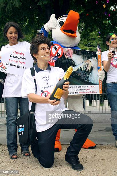 Supporters of 'The Bird Feeding Law' including one dressed as a Duck drink a toast as they demonstrate on July 12 in front of the US Embassy in Paris...