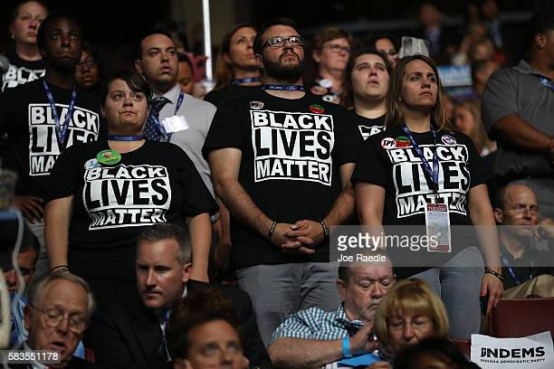 Supporters of the Black Lives Matter movement stand during remarks from the Mothers of the Movement on the second day of the Democratic National...