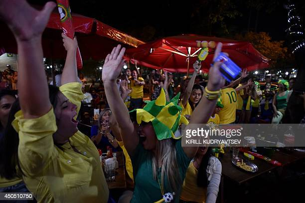 Supporters of the Brazilian national football team celebrate their team's win in a cafe in Itu on June 12 2014 during a live screening of a 2014 FIFA...