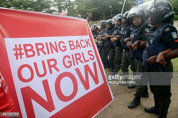 Supporters of the #BringBackOurGirls campaign hold a placard as policewomen block supporters of the 219 Chibok schoolgirls kidnapped by Boko Haram...