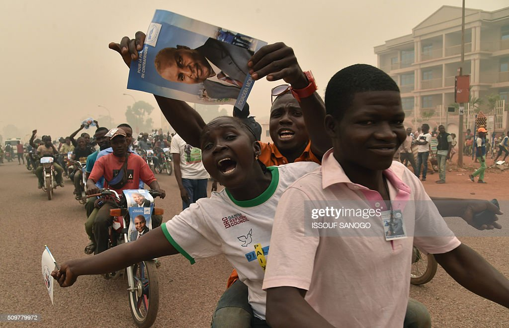 Supporters of the Central African Republic second round presidential candidate Anicet Georges Dologuele hold up his photo as they parade during his presidential campaign in Bangui, on February 12, 2016, ahead of the Febuary 14 presidential and legislatives elections. / AFP / ISSOUF SANOGO