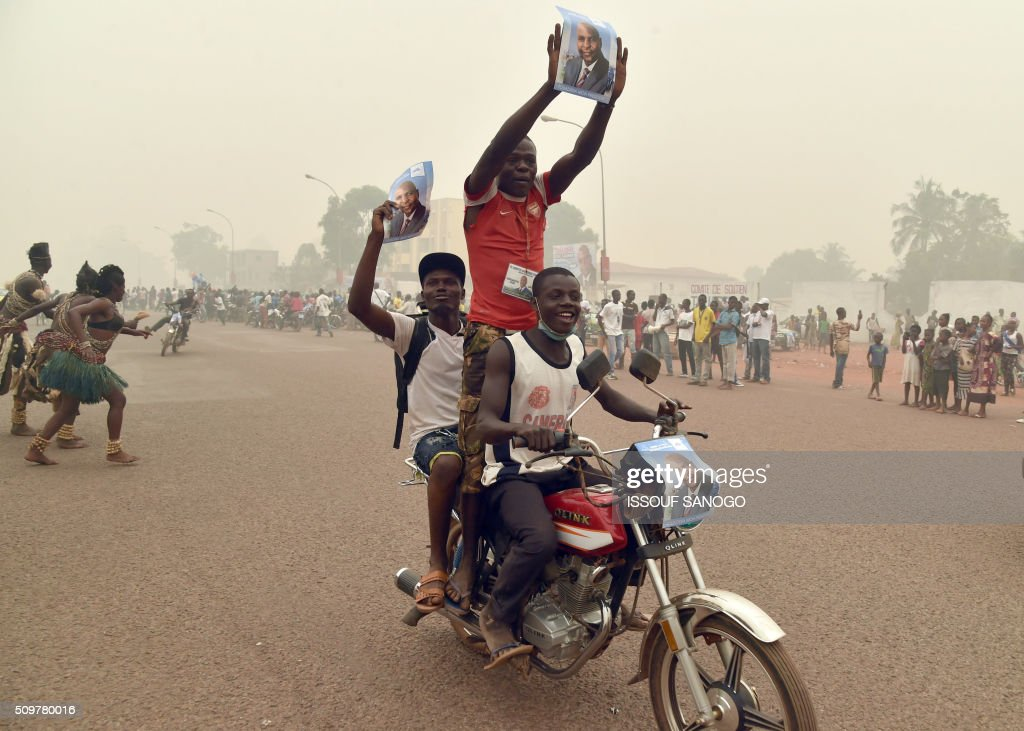 Supporters of the Central African Republic second round presidential candidate Anicet Georges Dologuele hold up his photo as they parade on a motor bike during his presidential campaign in Bangui, on February 12, 2016, ahead of the Febuary 14 presidential and legislatives elections. / AFP / ISSOUF SANOGO