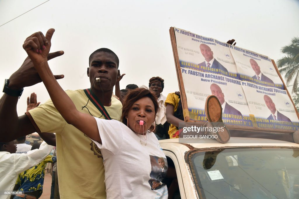 Supporters of the Central African Republic second round presidential candidate Anicet Georges Dologuele ride on the back of a flatbed lorry as they parade hrough the streets during his presidential campaign in Bangui, on February 12, 2016, ahead of the Febuary 14 presidential and legislatives elections. / AFP / ISSOUF SANOGO