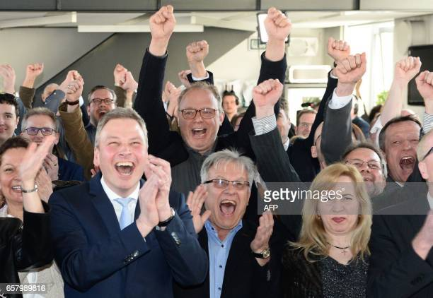 TOPSHOT Supporters of the Christian Democratic Union react after exit poll results of the state election in Saarland were announced on public TV at...