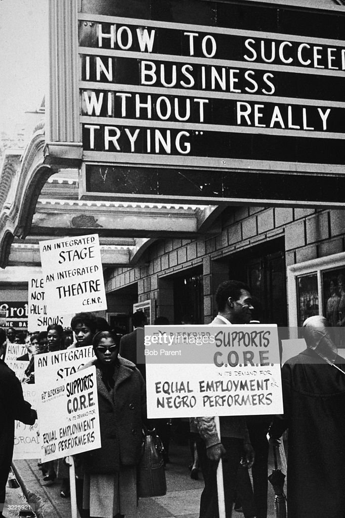Supporters of the Committee for the Employment of Negro Performers marching with placards in front of a theater in New York City. The marquee above advertizes the musical, 'How to Succeed in Business Without Really Trying'.