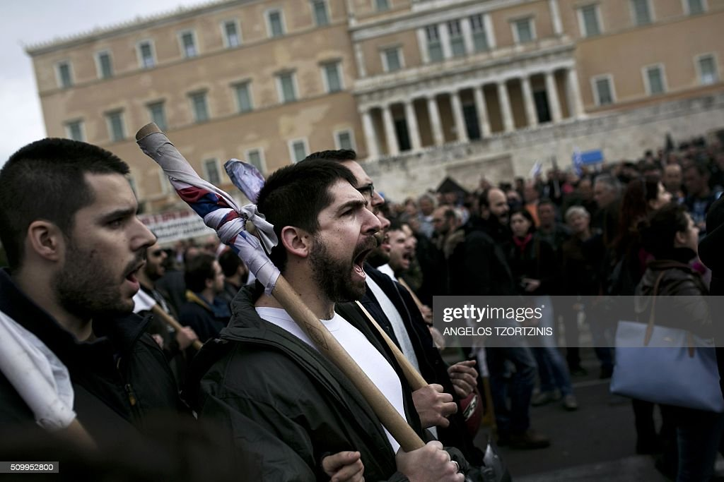 Supporters of the Communist-affiliated trade union PAME shout a slogan during a protest against pension reform and tax issues, on February 13, 2016 in Athens. Thousands of protesters, especially Supporters of the Communist-affiliated trade union PAME and farmers have again demonstrated on February 13 in Syntagma Square in Athens against a controversial project of pension reform. / AFP / ANGELOS TZORTZINIS
