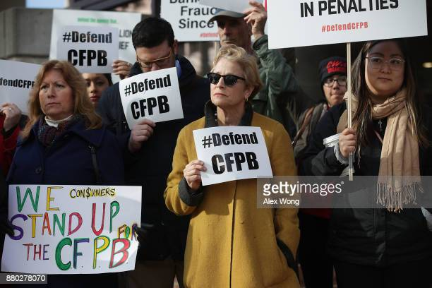 Supporters of the Consumer Financial Protection Bureau hold signs as they gather in front of the agency November 27 2017 in Washington DC President...