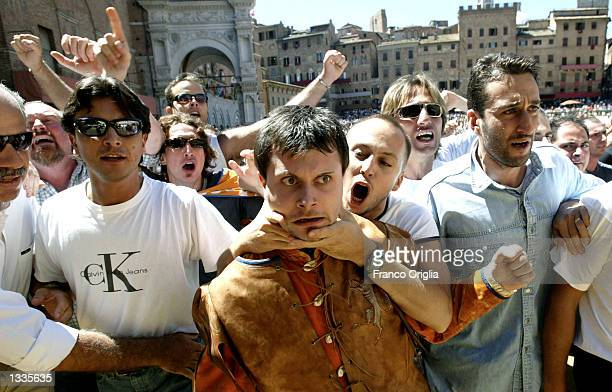 Supporters of the 'Contrada of Leocorno' or the Unicorn scream and cheer for the horse during the Il Palio horse race August 14 2002 in Siena Italy...