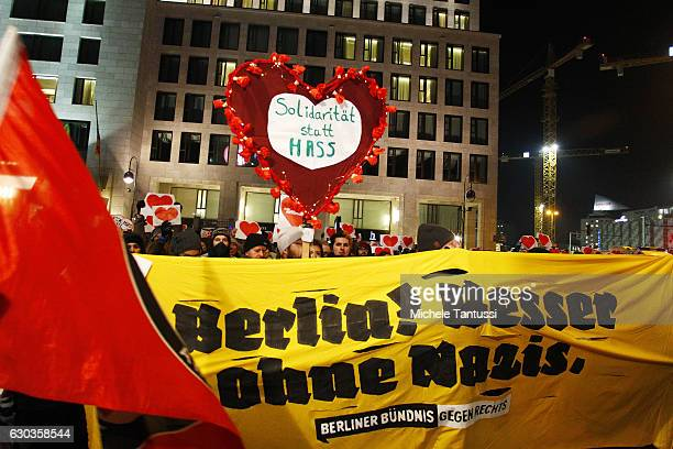 Supporters of the farLeft movement hold placards depicting a heart and a banner reading 'Berlin is better without nazis' as they hold a...