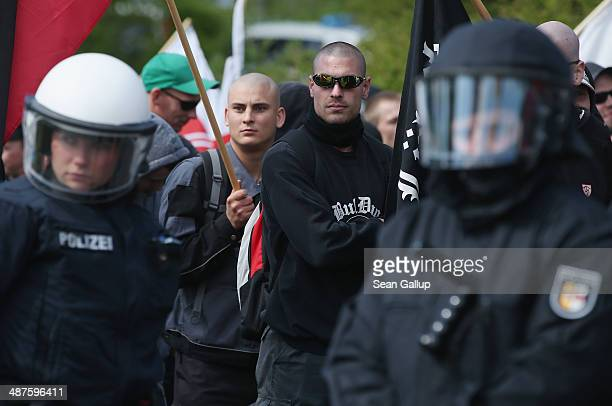 Supporters of the farright NPD political party accompanied by riot police march on May Day on May 1 2014 in Rostock Germany Leftwing protesters...