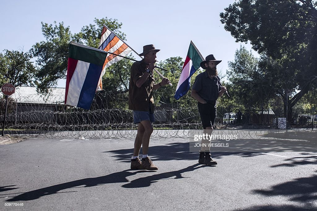 Supporters of the four men accused of murdering two farm workers stand outside of the magistrates court in Parys, Freestate, on February 12, 2016, flying the 'Four Colour' flag of the old Republic Of The Transvaal and the old flag of the Republic Of The Freestate. / AFP / JOHN WESSELS