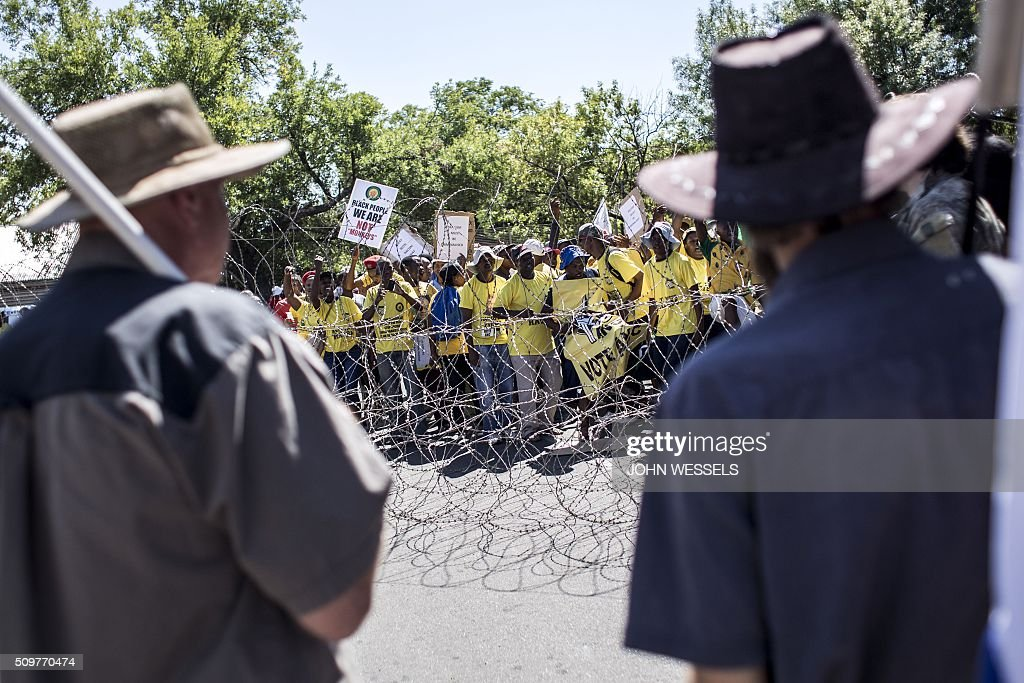 Supporters of the four men accused of murdering two farm workers stand outside of the Magistrates Court in Parys, Freestate, on February 12, 2016 flying the 'Four Colour' flag of the Old Republic Of The Transvaal whilst National African Congress(ANC) supporters sing and dance to protest against racism. / AFP / JOHN WESSELS