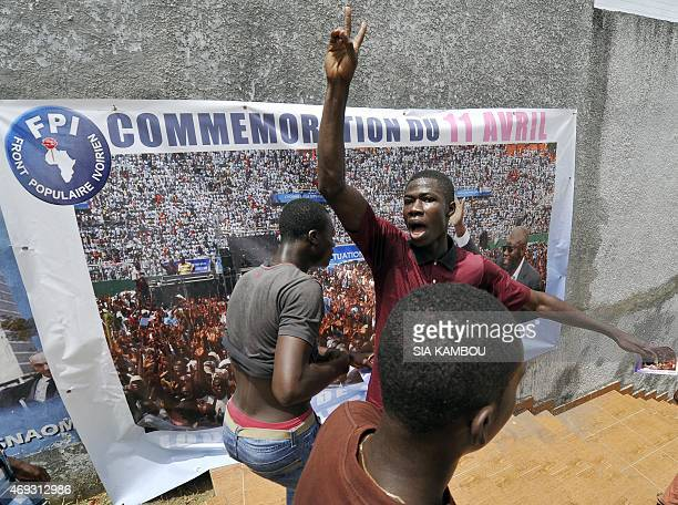 Supporters of the FPI the party of Ivory Coast's former president Laurent Gbagbo gesture in front of a banner picturing Gbagbo and reading in French...