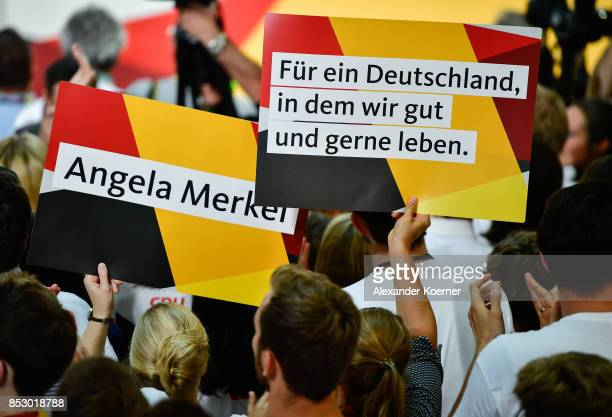 Supporters of the German Christian Democrats the party of German Chancellor Angela Merkel react to initial results that give the party 327% of the...