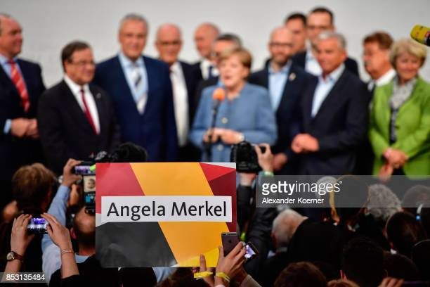 Supporters of the German Christian Democrats the party of German Chancellor Angela Merkel react to initial results that give the party 33% of the...