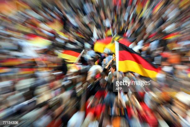 Supporters of the German national women's football team celebrate with the German flag as they wait for the arrival of the team 01 October 2007 at...