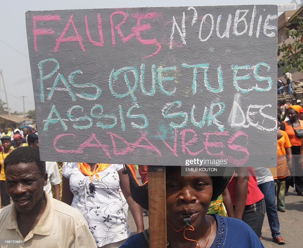 Supporters of the government protest in the streets of Lome on January 19, 2013 following fires of alleged criminal origin that ravaged two major markets in the country. Kara market some 420km north of the capital and the main building of Lome's largest market Adwalto were serverley damaged last week floowing the blazes. Placard reads, 'Faure d'ont forget you are sitting on cadavres' AFP PHOTO / Emile KOUTON