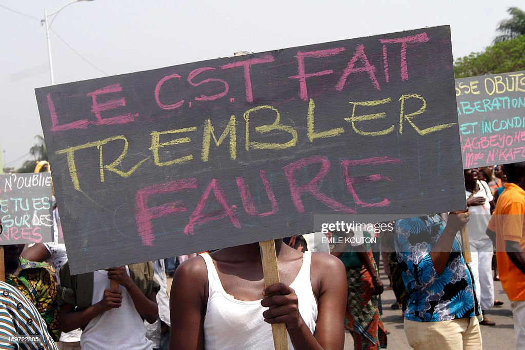 Supporters of the government protest in the streets of Lome on January 19, 2013 following fires of alleged criminal origin that ravaged two major markets in the country. Kara market some 420km north of the capital and the main building of Lome's largest market Adwalto were serverley damaged last week floowing the blazes. Placard read, ' the CST makes Faure tremble' AFP PHOTO / Emile KOUTON